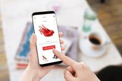 Añada a los zapatos rojos del carro en tienda en línea Teléfono elegante moderno con los bordes redondos en mano de la mujer Foto de archivo libre de regalías