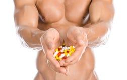 Añadidos del levantamiento de pesas y de la sustancia química: píldoras coloreadas tenencia fuerte hermosa del culturista aislada Imágenes de archivo libres de regalías