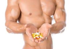 Añadidos del levantamiento de pesas y de la sustancia química: píldoras coloreadas tenencia fuerte hermosa del culturista aislada Imagen de archivo