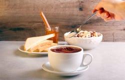 Añadiendo el azúcar en té en una taza, Fotos de archivo