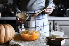 Añadiendo el azúcar marrón en la pasta para la descarga de la calabaza apelmácese Foto de archivo