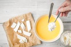 Añadiendo el queso en el huevo sauce la visión superior Fotografía de archivo