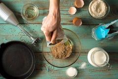 Añadiendo la harina en el bol de vidrio para cocinar la opinión superior de las crepes Imagen de archivo