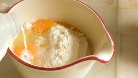 Añadiendo la leche a los huevos y a la harina para hacer que un talud se mezcla en un jarro almacen de video