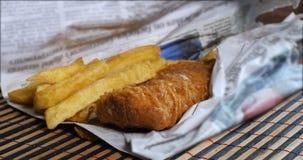 Añadiendo la sal y el vinager en pescado frito con patatas fritas ingleses envueltos en periódico almacen de metraje de vídeo