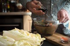 Añadiendo la salsa de soja en el adobo para el kimchi horizontal Imagenes de archivo