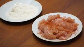 Añadiendo las especias a un plato de la carne, cocinando la comida en la cocina casera almacen de video