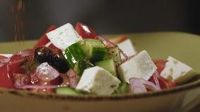 Añadiendo las especias vistió y preparó la ensalada griega tradicional en la cámara lenta almacen de video