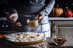 Añadiendo las galletas ralladas en la pasta para la descarga de la calabaza se apelmazan Fotografía de archivo libre de regalías