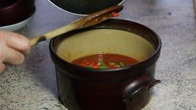 Añadiendo los ingredientes a cocinar el pote para un chile almacen de video