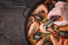 Añadiendo los mejillones en la cacerola con cocinar la opinión superior de la paella Imagenes de archivo