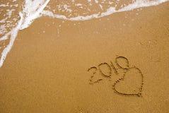 Año 2010 escrito en la arena Foto de archivo