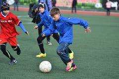 Año de Orenburg, Rusia 26 de abril de 2017: el fútbol del juego de los muchachos Imagen de archivo libre de regalías