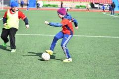 Año de Orenburg, Rusia 26 de abril de 2017: el fútbol del juego de los muchachos Fotos de archivo libres de regalías