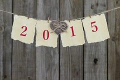 Año 2015 en el papel antiguo con la ejecución de madera del corazón en cuerda para tender la ropa por la cerca de madera Imágenes de archivo libres de regalías