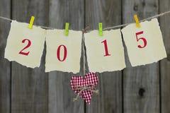 Año 2015 en el papel antiguo con la ejecución roja del corazón de la tela en cuerda para tender la ropa por la cerca de madera Imagen de archivo libre de regalías
