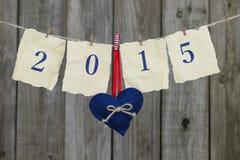 Año 2015 en el papel antiguo con la ejecución roja y azul del corazón en cuerda para tender la ropa por la cerca de madera lament Fotografía de archivo libre de regalías