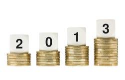 Año 2013 en pilas de monedas de oro con Backg blanco Imagenes de archivo