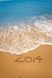 Año 2014 escrito en arena en la playa tropical Fotos de archivo