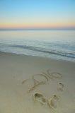 Año 2016 escrito en la playa arenosa en la puesta del sol Imagenes de archivo