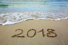 Año 2018 escrito en la playa del Caribe de la arena con la onda del mar Imagen de archivo