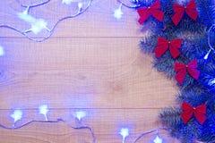 Año Nuevo/árbol de navidad con los arcos del rojo y la guirnalda azul en la plantilla de madera del fondo Foto de archivo