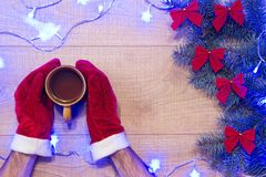 Año Nuevo/árbol de navidad con los arcos del rojo y la guirnalda azul en la plantilla de madera del fondo y manos en guantes rojo Imagenes de archivo