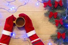 Año Nuevo/árbol de navidad con los arcos del rojo y la guirnalda azul en la plantilla de madera del fondo y manos en guantes rojo Imagen de archivo libre de regalías