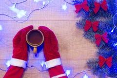 Año Nuevo/árbol de navidad con los arcos del rojo y la guirnalda azul en la plantilla de madera del fondo y manos en guantes rojo Fotografía de archivo libre de regalías