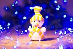 Año Nuevo/árbol de navidad con los arcos rojos, el juguete del muñeco de nieve y la guirnalda azul en la plantilla de madera del  Foto de archivo