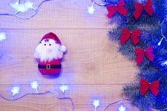 Año Nuevo/árbol de navidad con los arcos rojos, el juguete de Papá Noel y la guirnalda azul en la plantilla de madera del fondo Foto de archivo