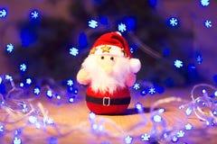 Año Nuevo/árbol de navidad con los arcos rojos, el juguete de Papá Noel y la guirnalda azul en la plantilla de madera del fondo Fotografía de archivo