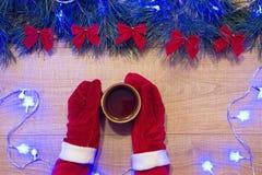 Año Nuevo/árbol de navidad con los arcos rojos, la guirnalda azul en la plantilla de madera del fondo y las manos en guantes rojo Fotos de archivo