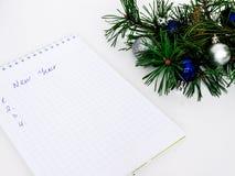 Año Nuevo, bolas de la Navidad, ramas del pino y un cuaderno Imagenes de archivo