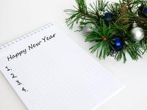 Año Nuevo, bolas de la Navidad, ramas del pino y un cuaderno Foto de archivo libre de regalías