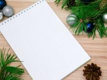 Año Nuevo, bolas de la Navidad, ramas del pino y un cuaderno Fotos de archivo