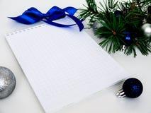 Año Nuevo, bolas de la Navidad, ramas del pino y un cuaderno Foto de archivo