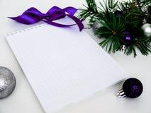 Año Nuevo, bolas de la Navidad, ramas del pino y un cuaderno Imagen de archivo