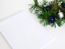 Año Nuevo, bolas de la Navidad, ramas del pino y un cuaderno Fotografía de archivo