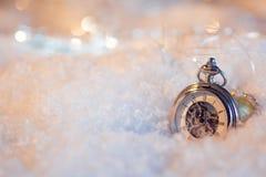 Año Nuevo, casi de medianoche Fondo festivo, reloj antiguo en la nieve Fotografía de archivo