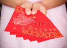 Año Nuevo chino feliz, mano de la mujer que sostiene el sobre rojo Foto de archivo