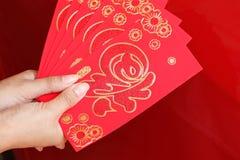 Año Nuevo chino feliz, mano de la mujer que sostiene el sobre rojo Fotos de archivo libres de regalías