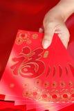 Año Nuevo chino feliz, mano de la mujer que sostiene el sobre rojo Imagen de archivo libre de regalías