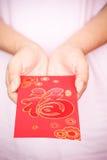 Año Nuevo chino feliz, mano de la mujer que sostiene el sobre rojo Fotografía de archivo
