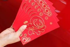 Año Nuevo chino feliz, mano de la mujer que sostiene el sobre rojo del regalo Foto de archivo libre de regalías