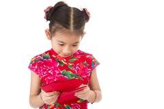 Año Nuevo chino feliz muchacha asiática de la sonrisa que sostiene el sobre rojo Fotografía de archivo