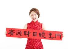 Año Nuevo chino feliz mujer asiática que muestra los pareados rojos Imagen de archivo libre de regalías