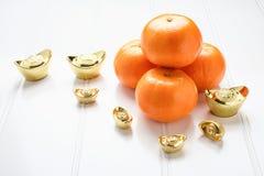 Año Nuevo chino, lingotes del oro y naranjas de la mandarina en la madera blanca Fotografía de archivo