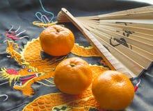 Año Nuevo chino, mandarinas y una fan que miente en la tela de seda con un dragón bordado Imágenes de archivo libres de regalías