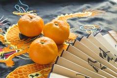 Año Nuevo chino, mandarinas y una fan que miente en la tela de seda con un dragón bordado Imagenes de archivo